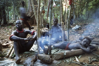 Members of a Jarawa community lie near a wood fire in their